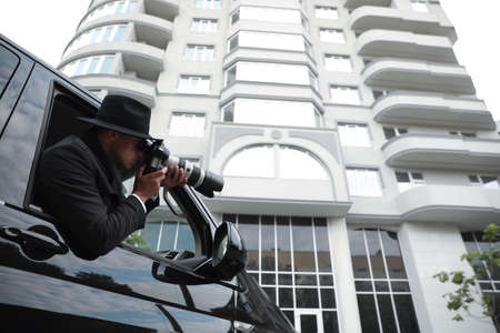Private detective with camera spying from car, low angle view Imagens