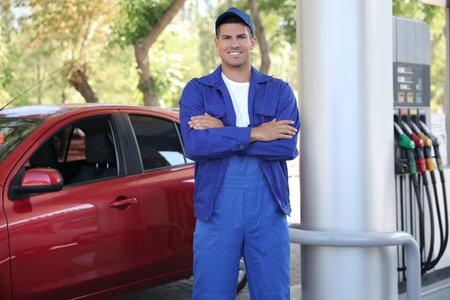 Worker in uniform at modern gas station