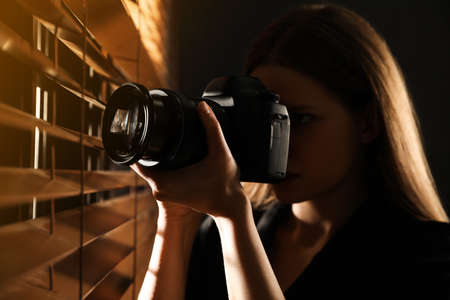 Private detective with camera spying near window indoors