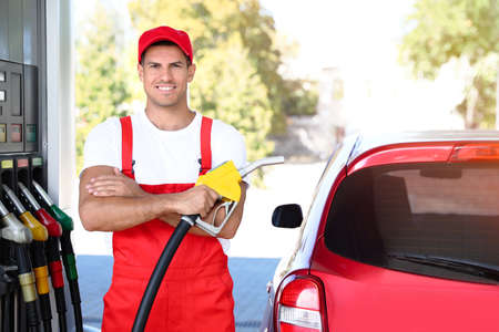 Worker with fuel pump nozzle near car at modern gas station