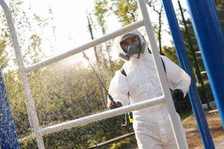 Man in hazmat suit spraying disinfectant on outdoor gym's equipment. Surface treatment during coronavirus pandemic