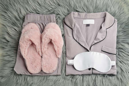 House slippers, sleeping mask and pajamas on gray faux fur, flat lay