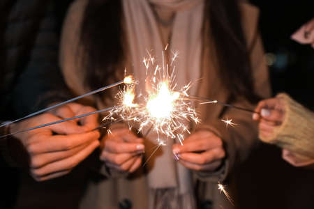 Group of people in warm clothes holding burning sparklers, closeup Standard-Bild
