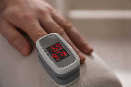 Man measuring oxygen level with modern fingertip pulse oximeter indoors, closeup. Space for text Stock Photo