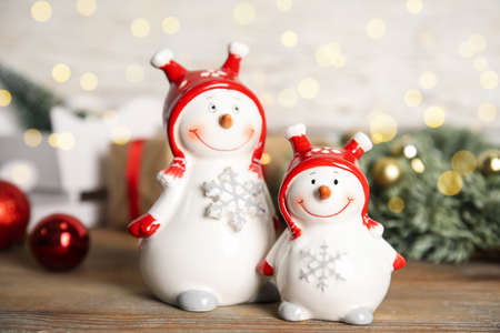 Funny little snowmen on wooden table. Christmas decor
