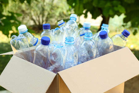 Cardboard box with used plastic bottles outdoors. Recycle concept Reklamní fotografie