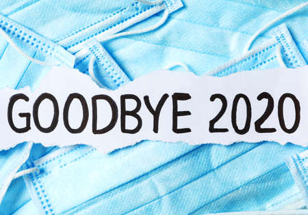 Piece of paper with phrase Goodbye 2020 on pile of blue medical masks. Coronavirus pandemic concept