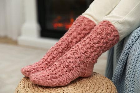 Woman wearing pink warm socks near fireplace, closeup