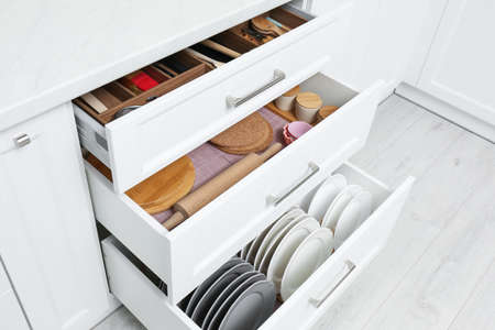 Open drawers with cutlery and utensils indoors. Order in kitchen