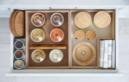 Open drawer with different jars indoors, top view. Order in kitchen
