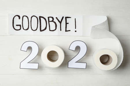 Text Goodbye 2020 and toilet paper on white wooden background, flat lay