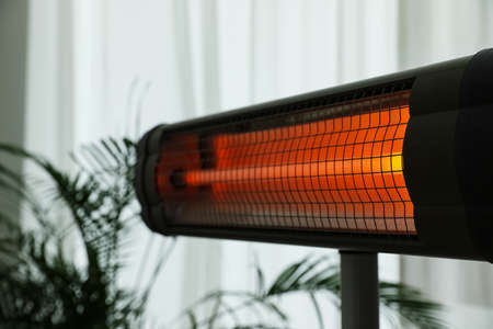 Modern electric infrared heater in room, closeup Imagens