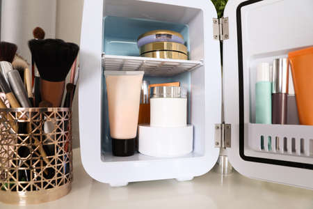 Mini fridge with cosmetic products on white vanity table, closeup