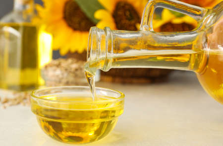 Pouring sunflower oil from jug into bowl on white table, closeup