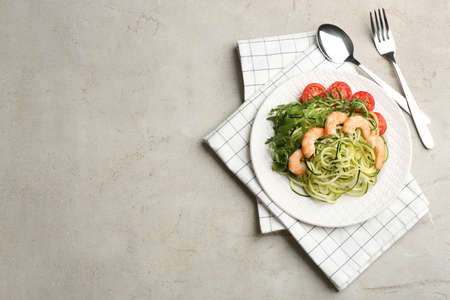 Delicious zucchini pasta with shrimps, cherry tomatoes and arugula served on light table, flat lay. Space for text
