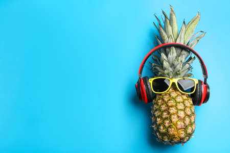 Top view of pineapple with headphones and sunglasses on light blue background, space for text. Creative concept