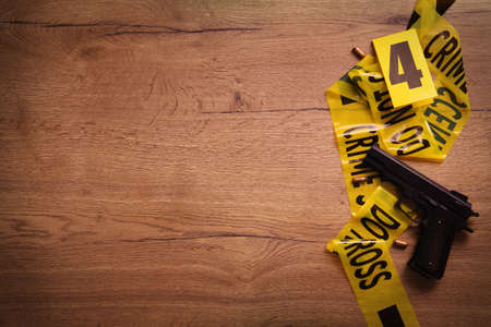 Flat lay with yellow tape, crime scene marker and gun on wooden background. Space for text Stockfoto