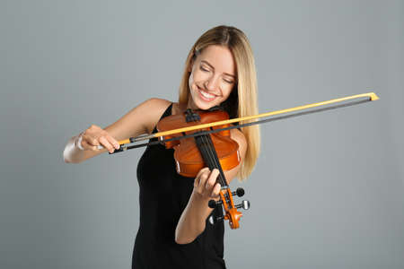 Beautiful woman playing violin on gray background