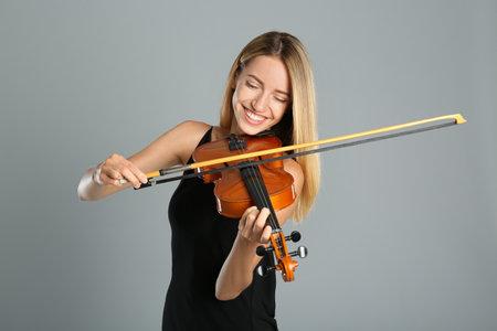 Beautiful woman playing violin on gray background