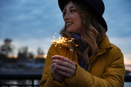 Woman in warm clothes holding burning sparkler outdoors Standard-Bild