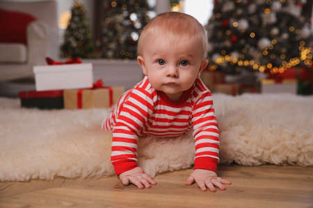 Cute baby in bright Christmas pajamas on floor at home Stock fotó