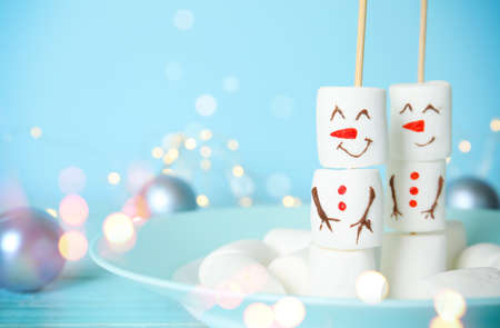 Funny snowmen made of marshmallows in plate, space for text. Bokeh effect