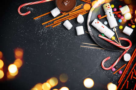 Flat lay composition with funny snowmen made of marshmallows on black table, space for text. Bokeh effect