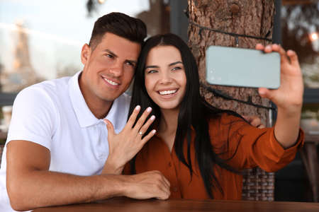Lovely couple taking selfie after they got engaged in outdoor cafe