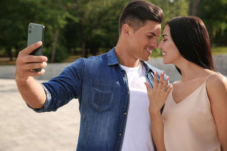 Lovely couple taking selfie after they got engaged outdoors