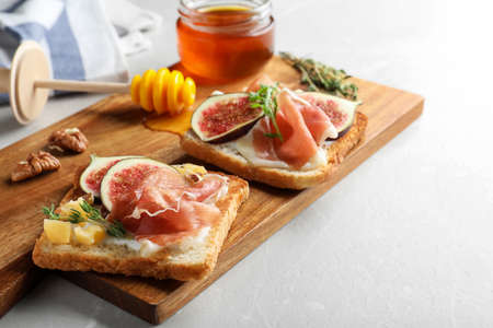 Delicious sandwiches with figs, proscuitto and cheese on light table, closeup