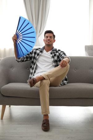 Man with hand fan sitting on sofa. Summer season