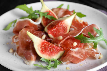Delicious figs and proscuitto on plate, closeup Standard-Bild