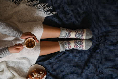 Woman in warm socks with cup of hot drink relaxing on knitted blanket, top view Stock Photo