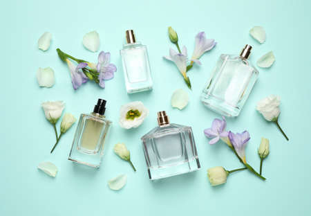 Flat lay composition with different perfume bottles and flowers on cyan background Stock Photo