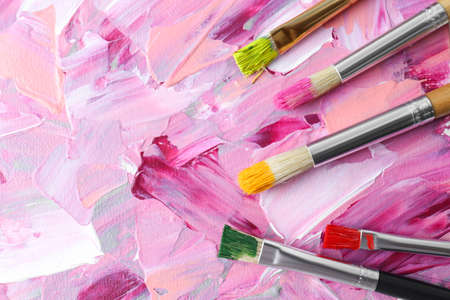 Set of different brushes on abstract colorful paint, flat lay