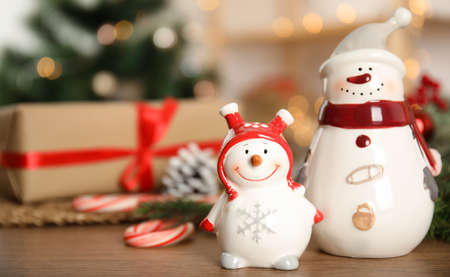 Christmas composition with decorative snowmen on wooden table, space for text