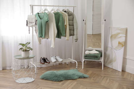 Rack with stylish warm clothes and shoes near mirror in dressing room