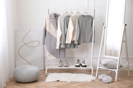 Rack with stylish warm clothes and mirror in dressing room