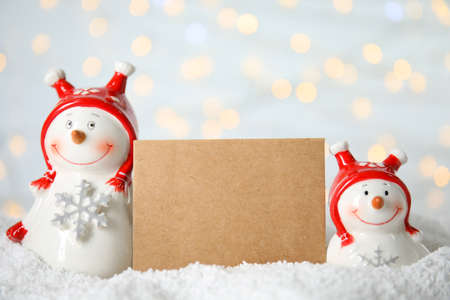 Decorative snowmen near blank greeting card on artificial snow against blurred festive lights, space for text