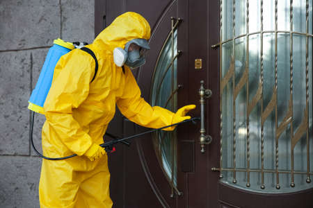 Person in hazmat suit disinfecting entrance door with sprayer. Surface treatment during coronavirus pandemic