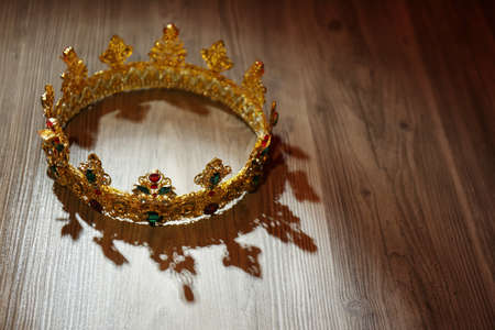 Beautiful golden crown with gems on wooden table. Fantasy item Фото со стока