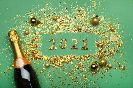 Flat lay composition with confetti, festive decor and bottle of champagne on green background. New Year celebration