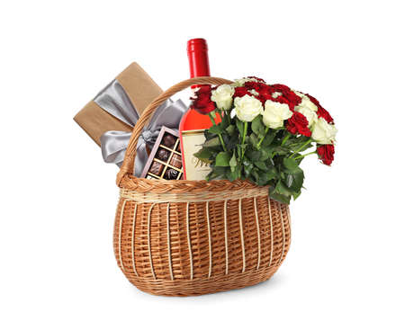 Wicker basket with gifts on white background