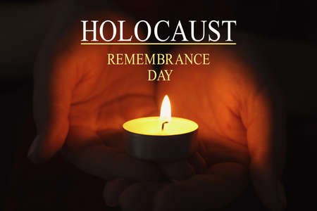 International Holocaust Remembrance Day. Woman holding burning candle in darkness, closeup