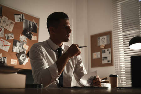 Detective working at desk in his office