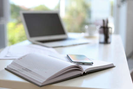 Planner and modern smartphone on table in office