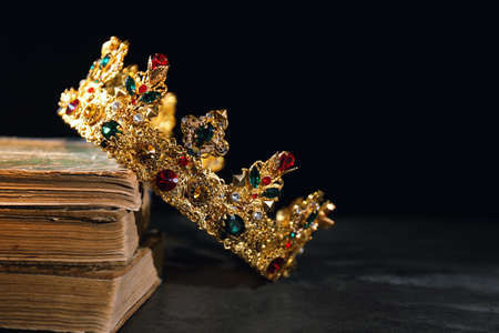 Beautiful golden crown and old books on black table, space for text. Fantasy item