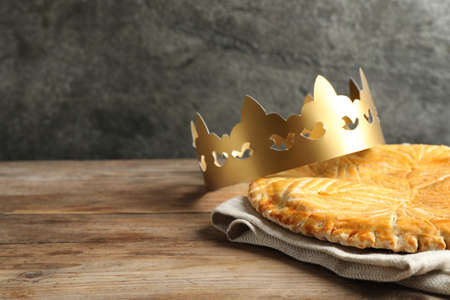 Traditional galette des Rois with paper crown on wooden table. Space for text