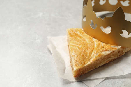 Slice of traditional galette des Rois with paper crown on light gray table. Space for text