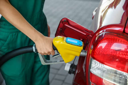 Young worker refueling car at modern gas station, closeup